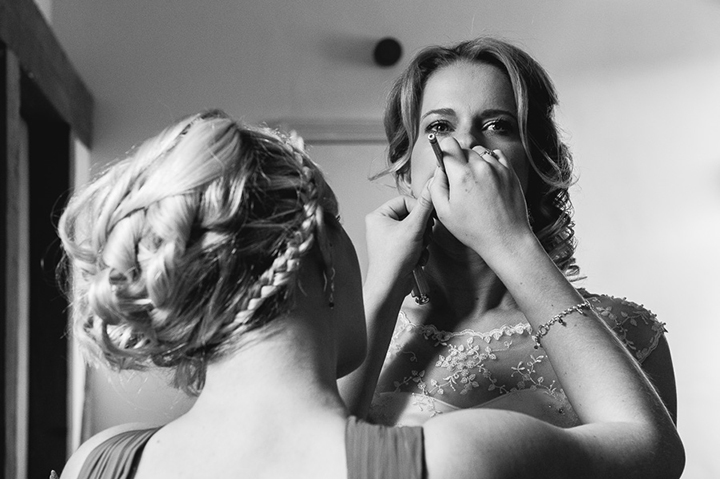 A bride has the finishing touches applied to her makeup before her wedding at Deer Park Hall in Eckington, Worcestershire. As a wedding photographer, Deer Park Hall has to be my favourite wedding venue! Wedding photography by Lee Webb