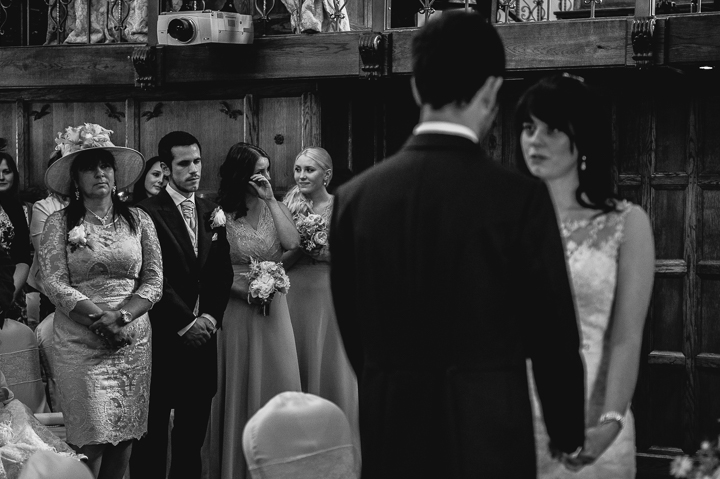 This perfectly timed wedding photo from Deer Park Hall in Worcestershire shows a bridesmaid wiping a tear from her face during the wedding ceremony. Deer Park weddings photographed by Lee Webb