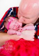 A very proud new Daddy giving newborn daughter a kiss