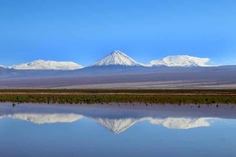 Rare reflection of volcanoes in flood water, near San Pedro