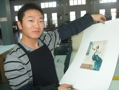 Liu Hong Liang proudly displays a print