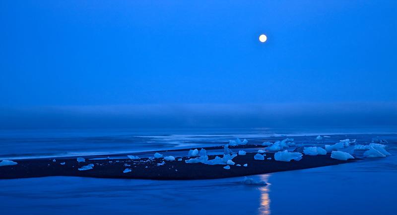 Icebergs sur un îlot au lever de pleine lune