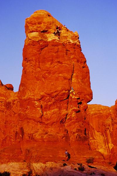 Alpinistes dans la section Windows au coucher du soleil - Arches NP, Utah