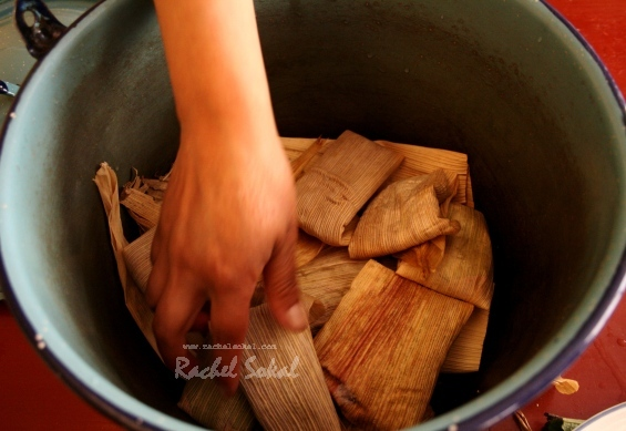 Juana puts the tamales into the pot - only one pair of hands, or they won't cook well!