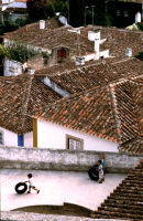 Children play on a rooftop in Obidos, Portugal. 2007