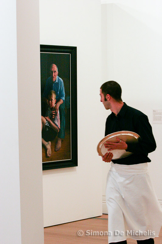 Waiter taking in exhibits at the BP Portrait Awards