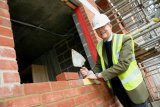 Mr John Harrison, Estates Bursar lays the golden brick.