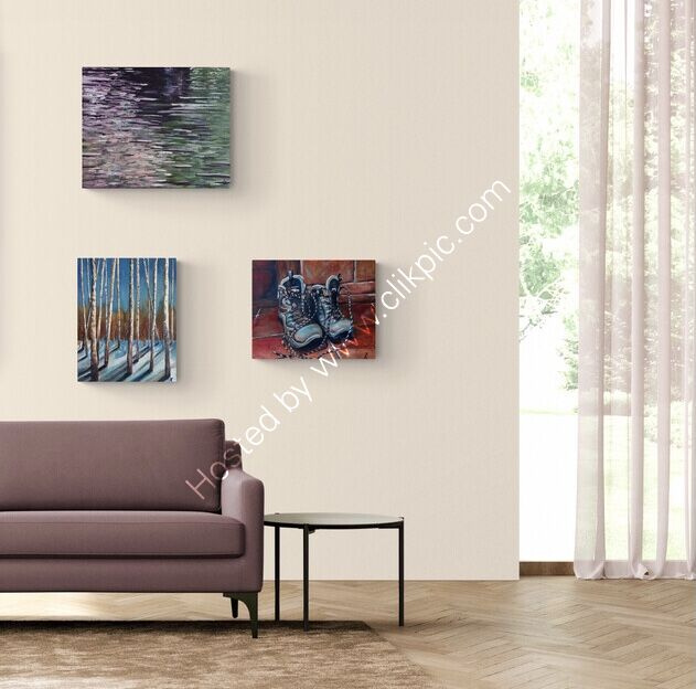 Three paintings displayed together in a room setting