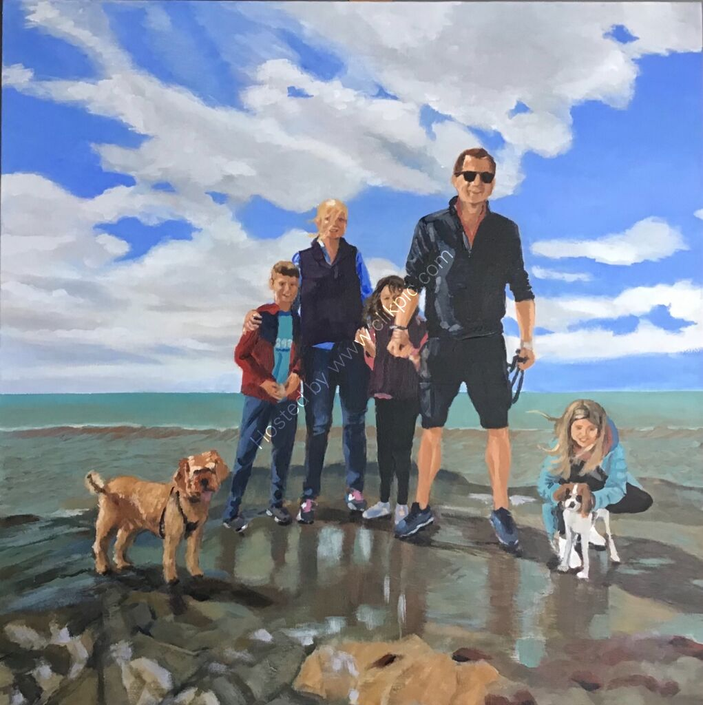 A family group including children and dogs on holiday standing in front of the sea