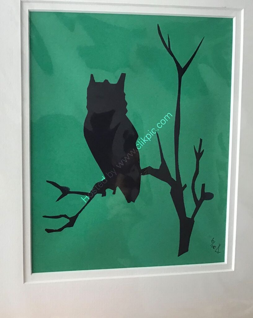 An etched owl printed as a silhouette in black on emerald green orange paper
