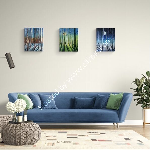 A row of three colourful abstracted paintings displayed over a blue sofa