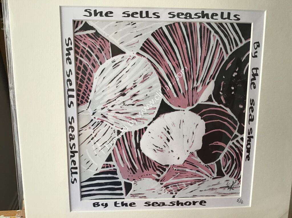 A linocut print of seashells in pink black and white with words around mount