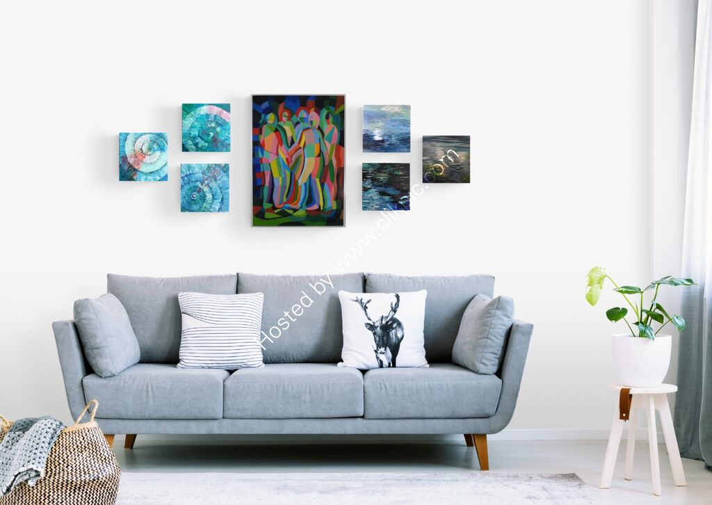 a cluster of paintings displayed over a comfy sofa