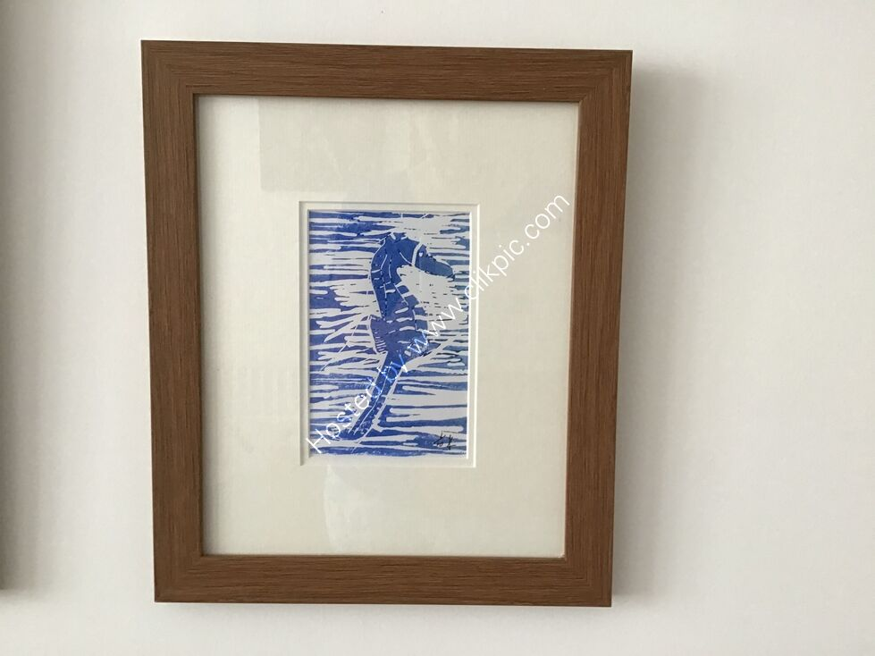 A linocut of a seahorse, printed in blue on white, framed