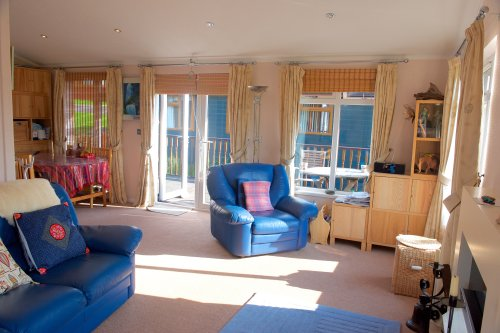 Living room looking towards french windows which open to the decking outside.