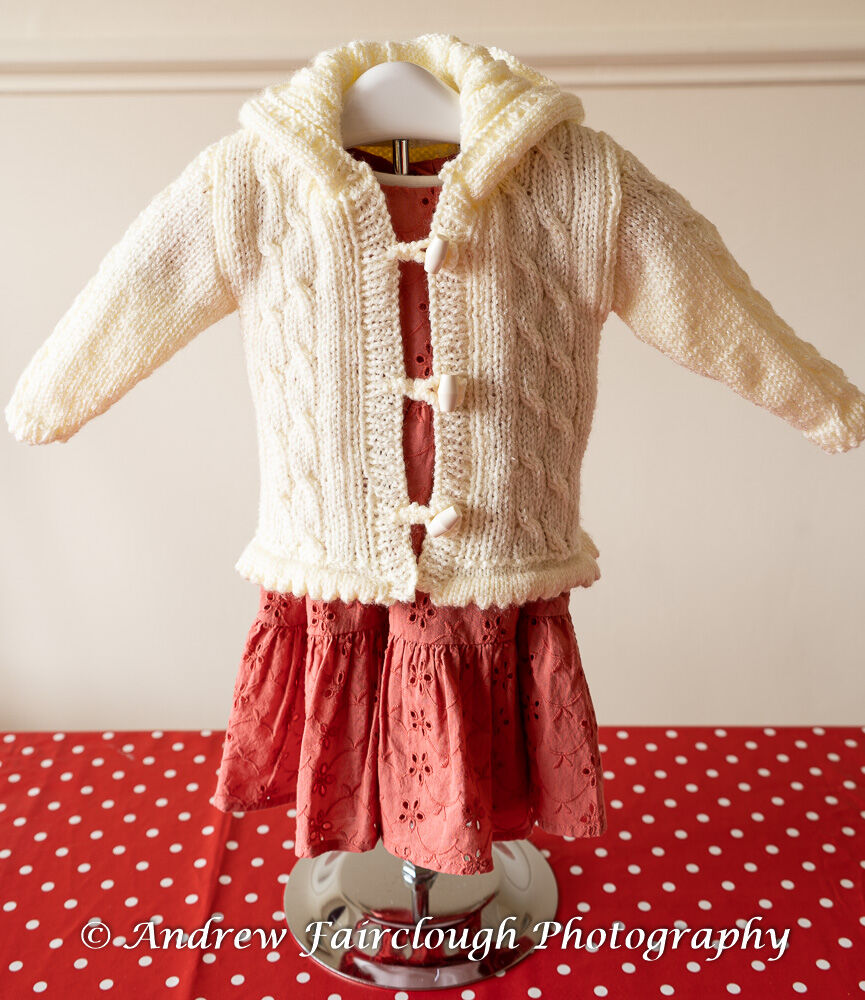Fluted Waistband and Cable Hooded Jacket in Cream Shimmer Yarn.
