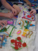 Everyone carefully adds their design to the main felt.