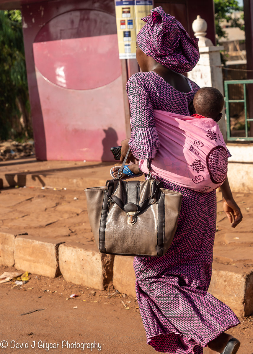 A lady carries her baby to work