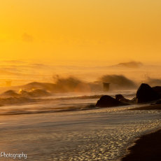 Sunrise and the waves breaking over the rocks