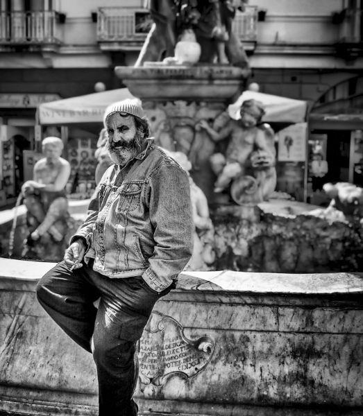 Smoking Man Sitting on a Fountain