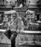 Smoking Man Sitting on a Fountain