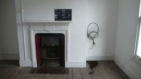 Roots <br> Installation at the Exhibition 'Surfaces Imbued' <br> Photograph, lead figure and root, 2008