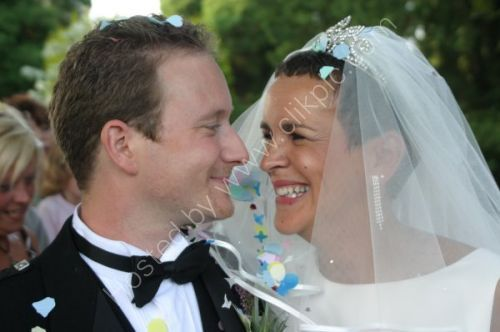 Newly weds smile into each others eyes.