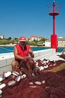 Fisherman repairing the net