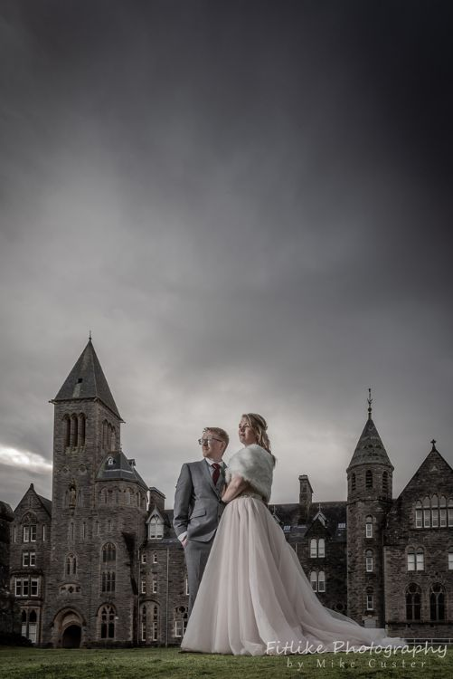 Elgin Wedding Photographer. Dark and moody on a rainy day.Bride & Groom in romantic pose outside an old abbey.