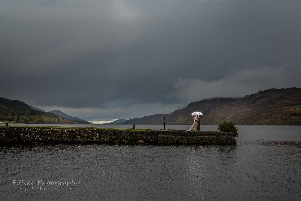 Bride & Groom in a romantic pose on a jetty looking up Loch Ness from Fort Augustus.