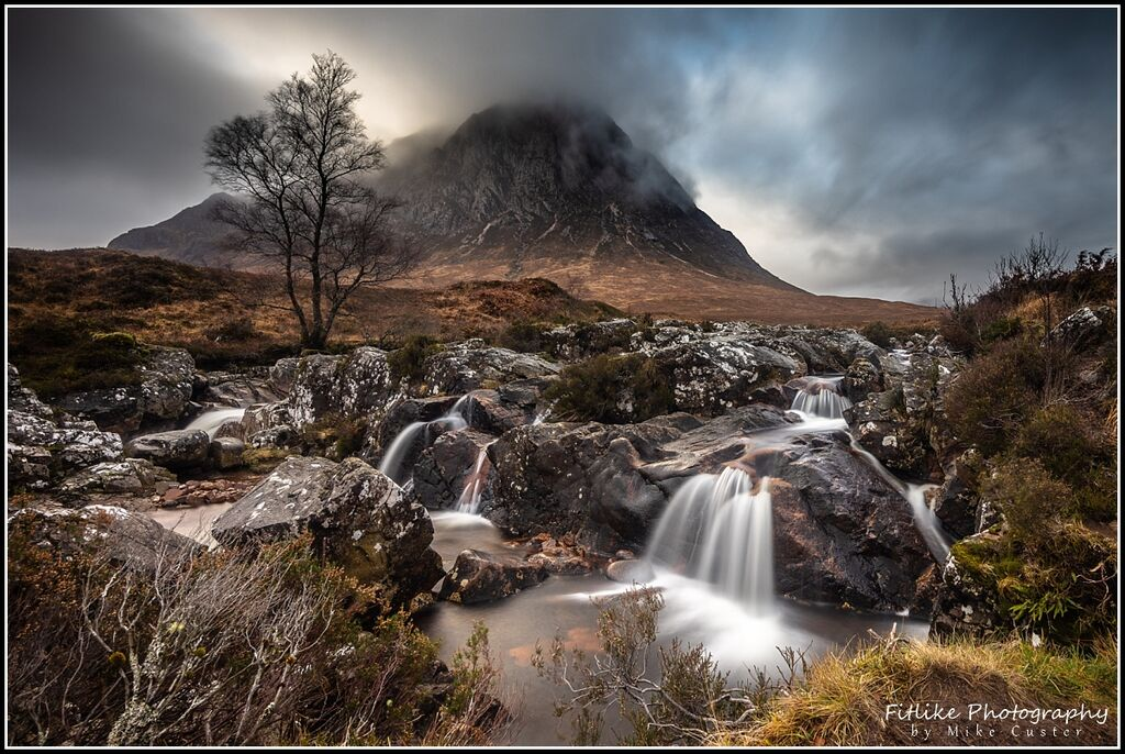 A Scottish landscape photograph of Buachaille Etive Mor. Taken with the stream and tree in the foreground.