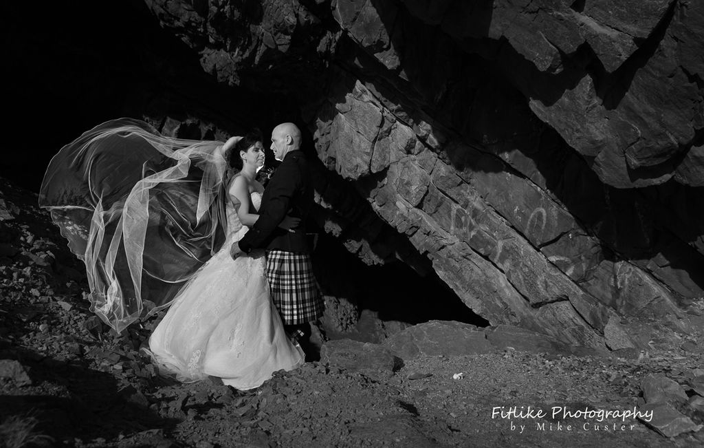 Bride and Groom in Romantic pose with a long veil. Lit by off camera flash.
