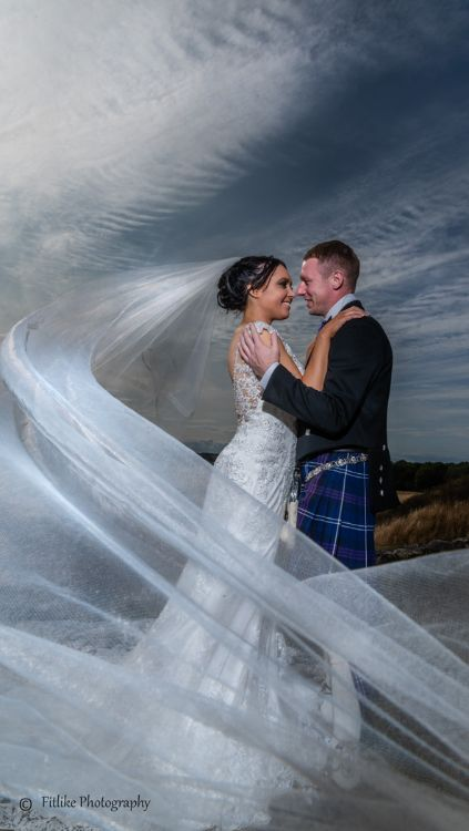 Bride and Groom in Romantic pose with a long veil. Lit by off camera flash. The reflection created in camera using a phone