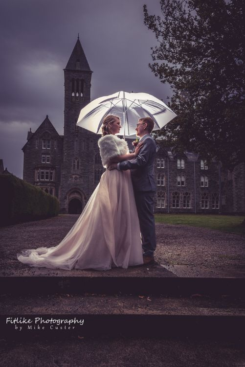 Bride and Groom in Romantic pose in front of an abbey. Lit by off camera flash from behind to separate them from the background.