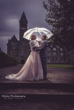 Bride and Groom in Romantic pose in front of The Highland Club, Fort Augustus, Inverness by Moray Wedding Photographer Mike Custer. Lit by off camera flash from behind to separate them from the background.
