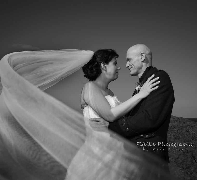 Bride & Groom posed to allow the long veil to bellow in the wind.