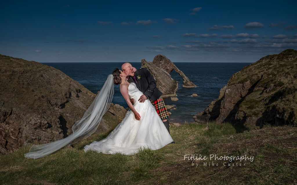 Bride and Groom in Romantic pose. Lit by off camera flash. Posed to replicate the angles of Bow Fiddle Rock, Portknockie, Moray, Scotland.