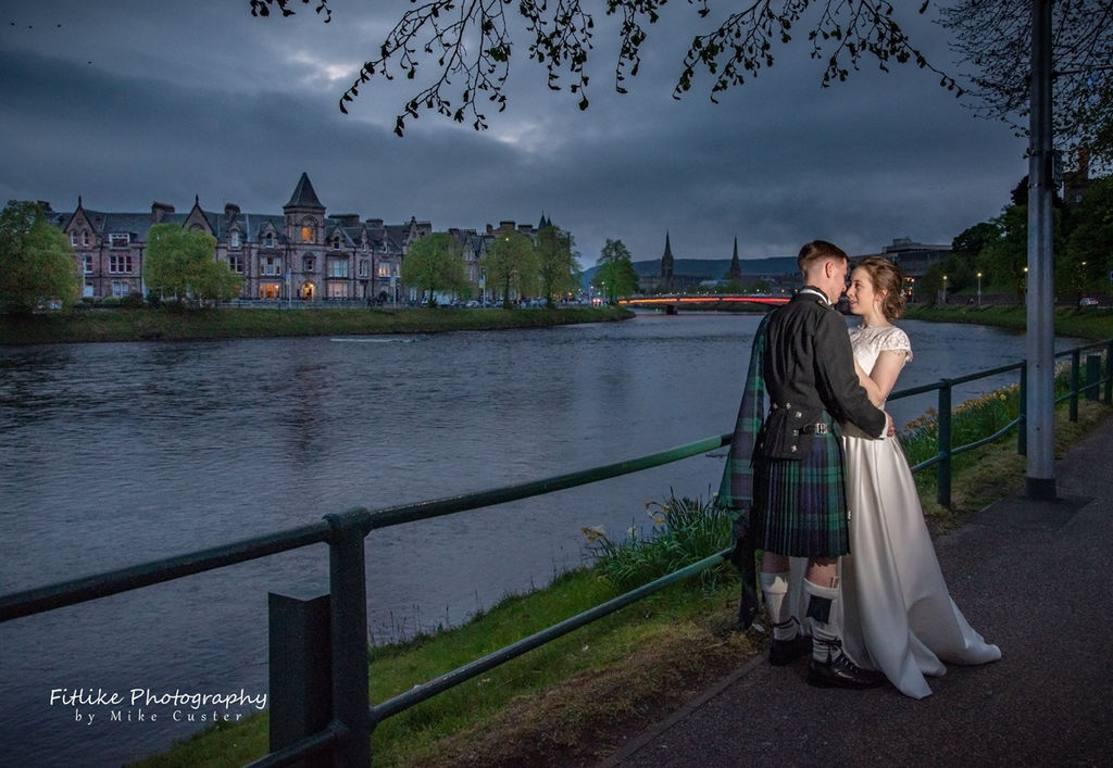 Bride & Groom holding hands in romantic pose at the river side. Taken at twilight