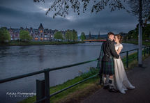 Bride & Groom holding hands in romantic pose at the side of the River Ness, Inverness.. Taken at twilight