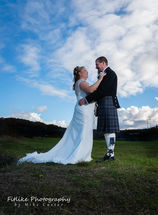 The bride and groom guided into a close embrace. Lit with off camera flash. On a sunny day in Banff, Aberdeenshire.