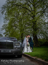Bride and Groom photographed with their wedding car. A Rolls Royce Phantom.