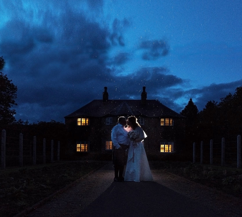 Photograph of the bride and groom taken at twilight using of camera flash with a cottage in the background.