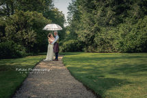 The bride and groom posed on a tree lined path on a sunny day.
