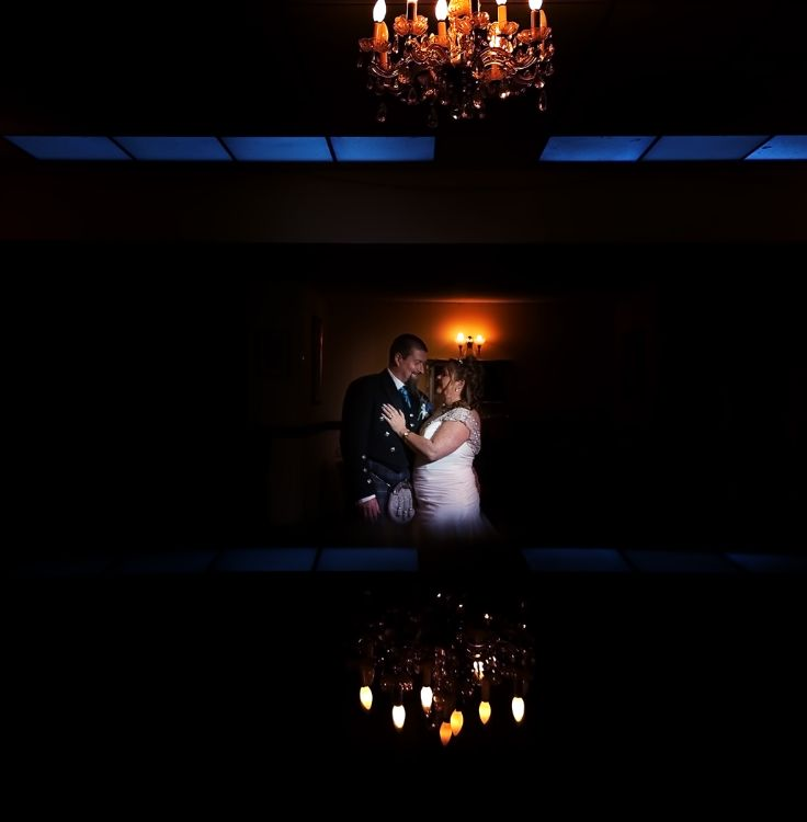Bride and Groom in Romantic pose. Lit by off camera flash. The reflection created in camera using a phone