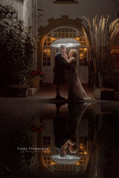Bride & Groom holding hands in romantic pose in a doorway of a hotel. A reflection created by a puddle on the ground.