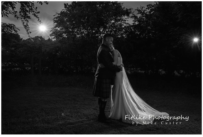 A wedding photography of the bride and groom posed with each other. Lit by 2 off camera flashes just behind and too the side of them.