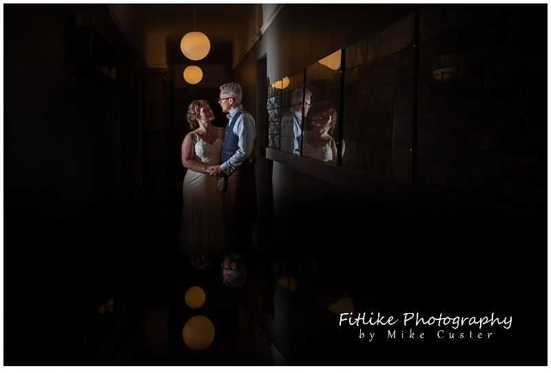 A wedding photograph of the couple posed in a hallway. With light fittings reflected below and the couple reflected in a picture frame.