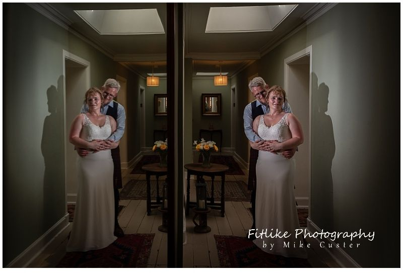 The bride and groom posed in a hallway of n old house in Dunkeld, Perthshire, Scotland. Positioned so that I could get a reflection in a wall mounted mirror.