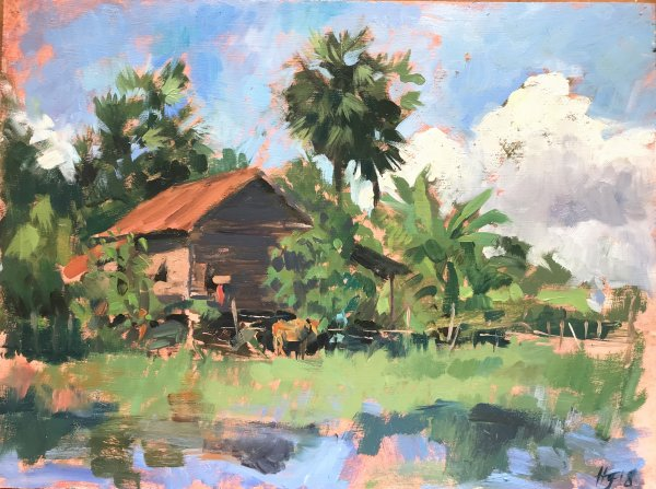 Cambodian rural landscape with cow shading beneath a tree