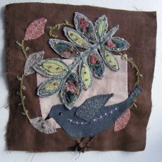 Textile bird and leaf.